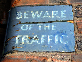 Painted sign on wall – Beware of the Traffic