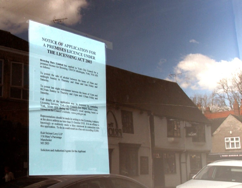 Licensing application document in Micklegate window, reflecting The Priory pub opposite, April 2016
