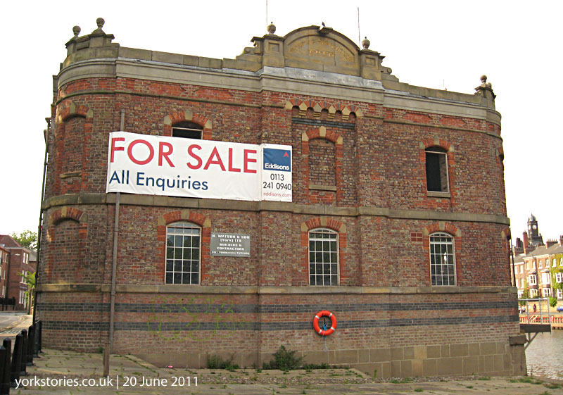Victorian riverside warehouse with For Sale sign