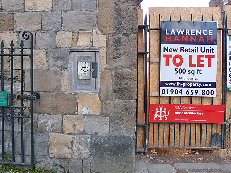 To Let sign on building site, and faded sign for toilet with wheelchair access symbol