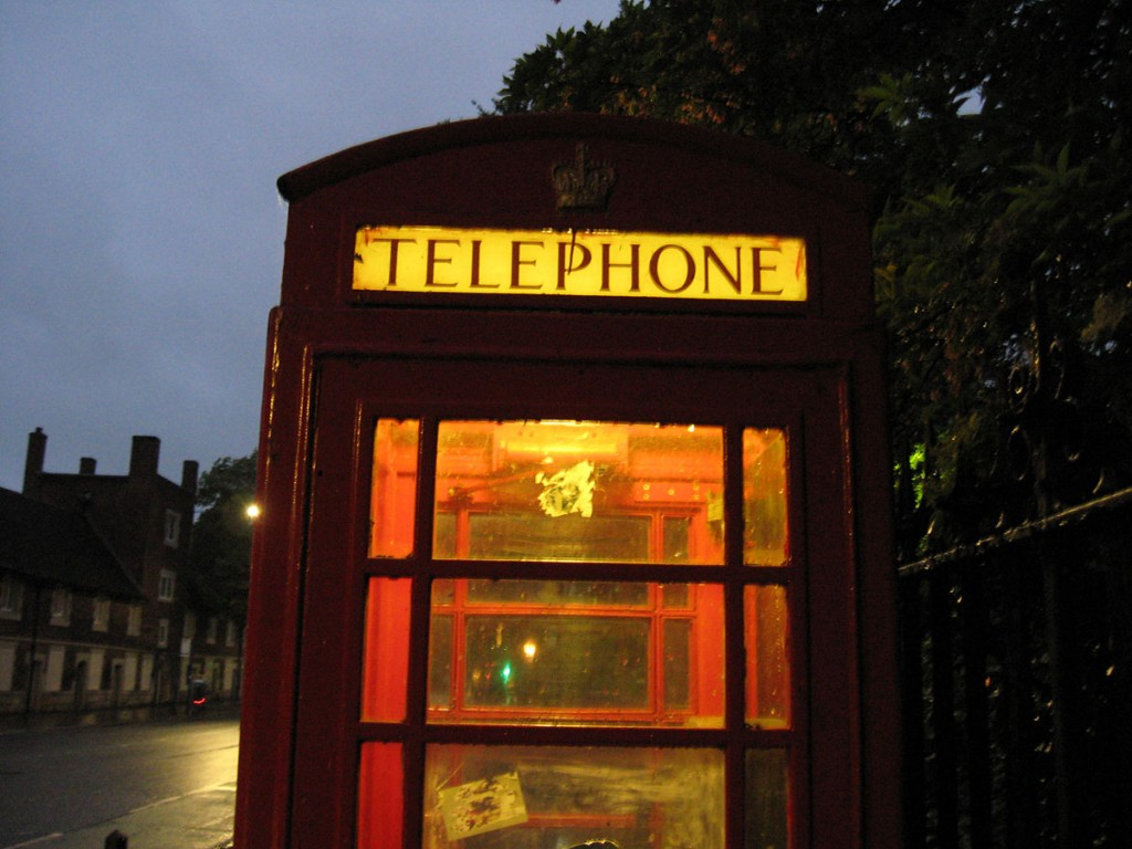 Phone box, illuminated from within, at dusk