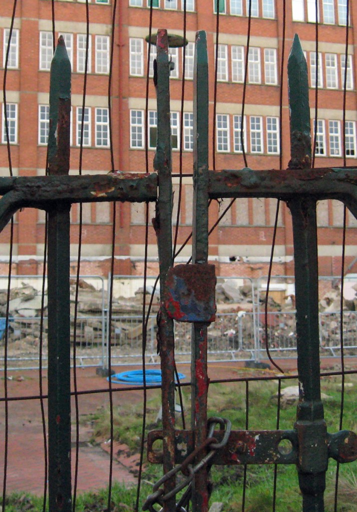 Rusty gates, old factory building in the background