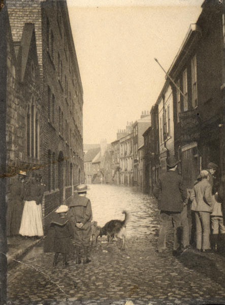 Old photo of people (and dogs) at end of flooded street