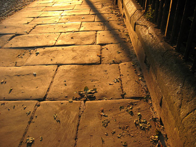 Old stone paving lit by low evening sunlight