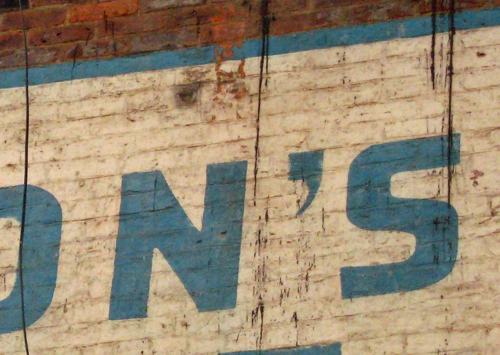 Apostrophe and lettering on painted wall advert