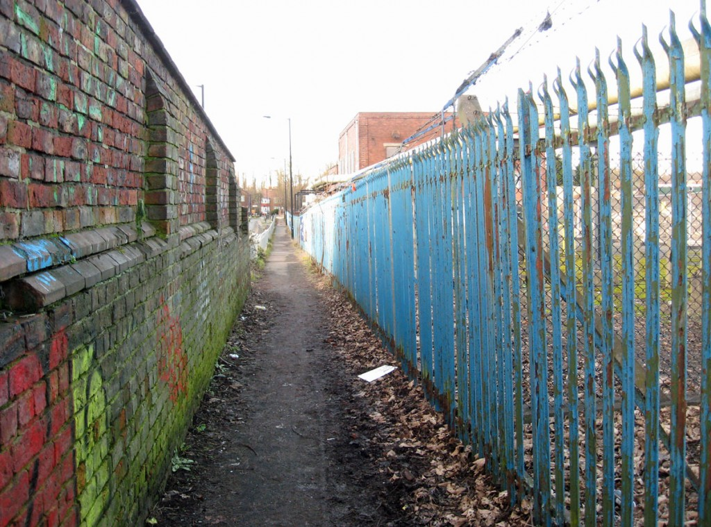 19th century brick wall on left, blue rusted railings on right