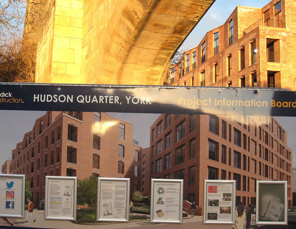 Information board for Hudson Quarter, with new buildings behind, arch overhead, sunlit