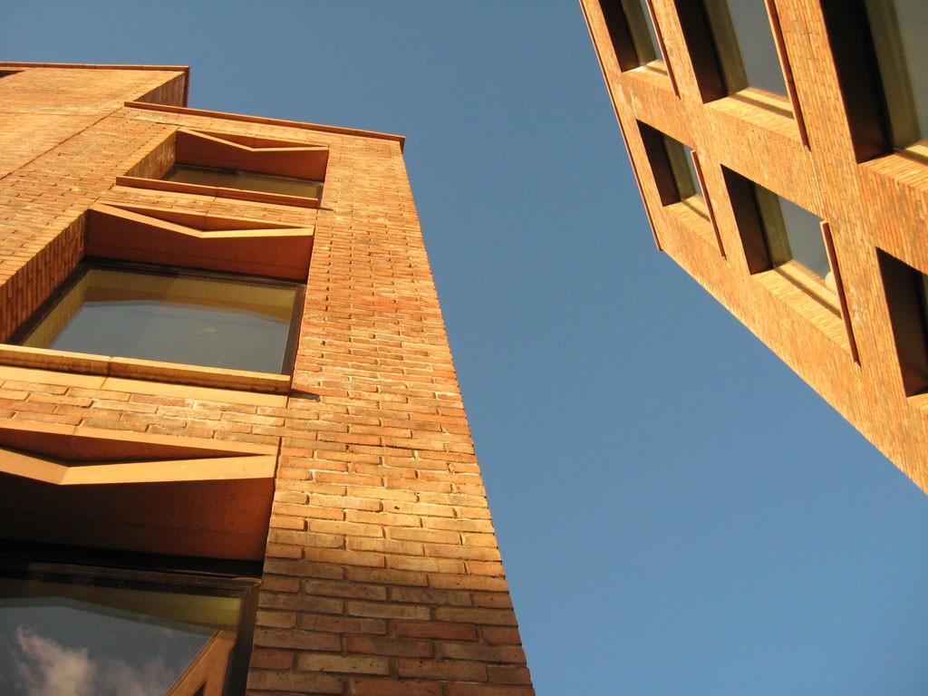 Brick buildings lit by warm evening sun, blue sky behind