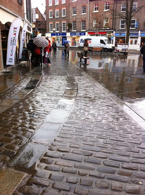 Old worn paving, rainy day, reflecting light