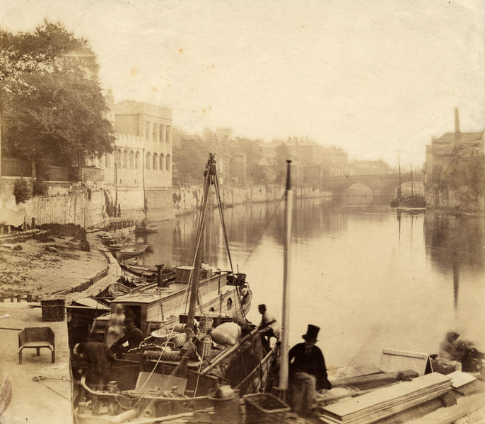 Old photo, men and boats on riverbank