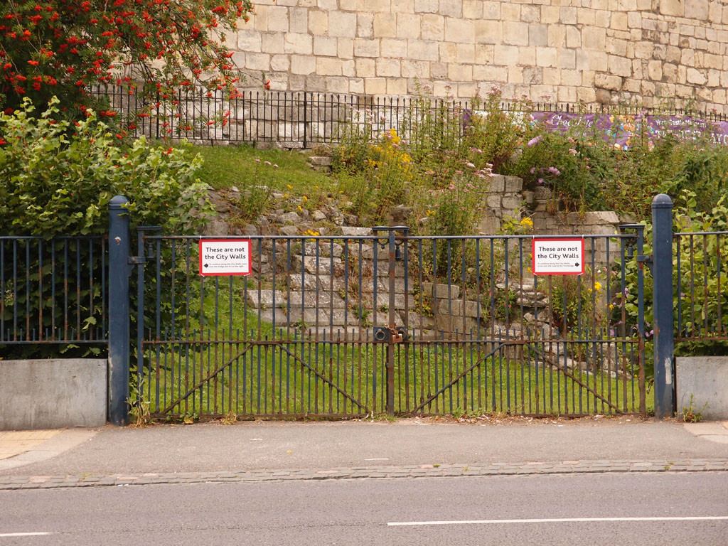 Signs by the castle walls: 'These are not the City Walls'