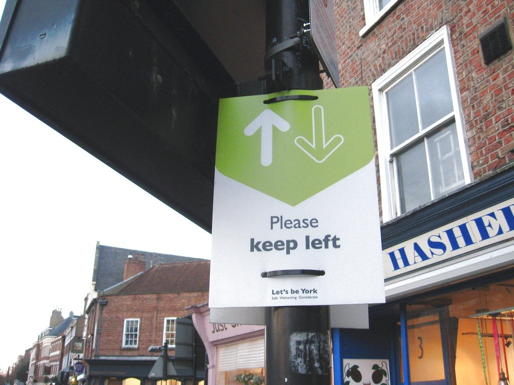 sign on lamp post, instruction to keep left