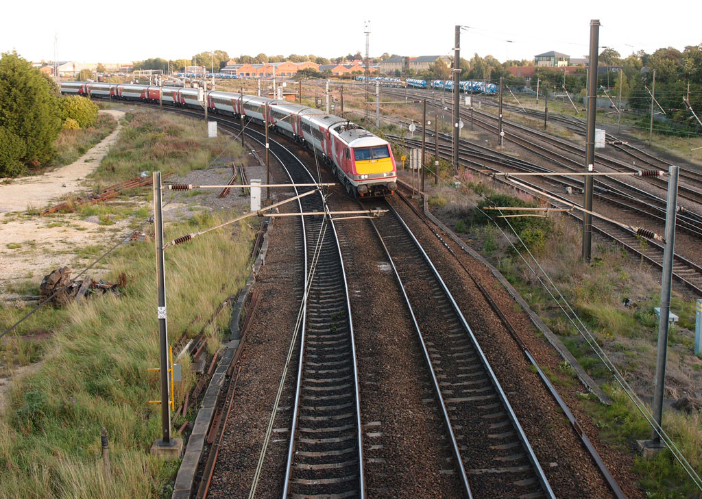View of railway lines, with train, buildings in distance