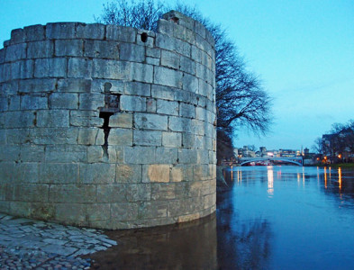 Medieval stone tower at water's edge, dusk