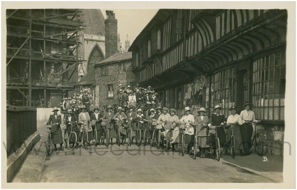Women with bicycles, and horse-drawn charabancs behind, outside St William's College, early 20th century. (More information:  cardindex.com)