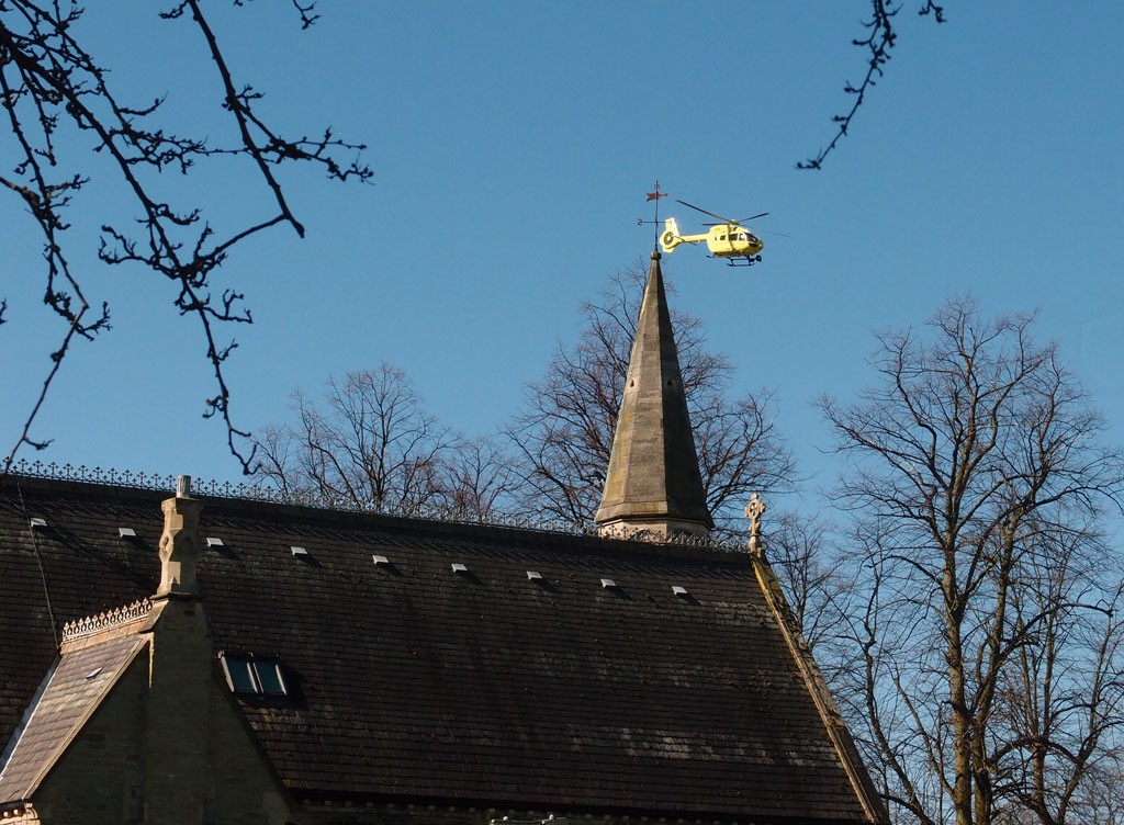 Yellow helicopter above spire, in blue sky